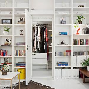 W pokoju dziennym całą ścianę zabudowano białą szafą z licznymi praktycznymi półkami. Mebel pełni funkcję praktycznej biblioteczki, jak i garderoby. Fot. Alvhem Makleri.