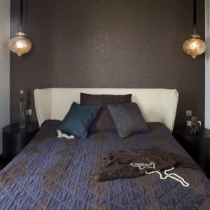 Tapeta umieszczona za łóżkiem stała się doskonałym tłem dla ekspozycji wiszących, orientalnych lamp umieszczonych po obu stronach łóżkach. W sypialni wytapetowano tylko jedną ścianę, pozostałe pomalowano na jasny kolor. Projekt: Katarzyna Szajbel - Żukowska. Fot. Marcin Onufryjuk.