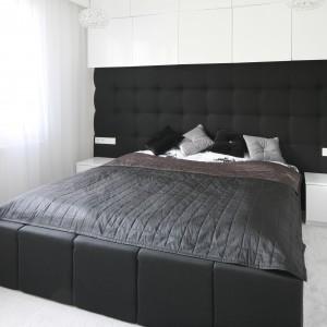 Na całej szerokości ściany umieszczono czarny, tapicerowany zagłówek, który tworzy przyjemny kontrast z jasną, wiszącą zabudową oraz białymi stolikami nocnymi. Projekt: Dominik Respondek. Fot. Bartosz Jarosz.