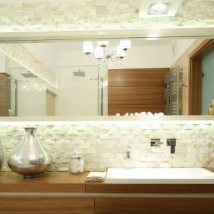 """Kamienna okładzina ściany została wykonana z łupanki kamiennej """"Guam"""" oferowanej w wygodnych do montażu panelach o wymiarach 60x15 cm. Ciepłe odcienie drewna i beżowy kamień to idealne połączenia barw i materiałów do łazienki rodzinnej. Wnętrze jest elegancie i zachowa urok i styl na lata.  Projekt: Małgorzata Mazur.Fot. Bartosz Jarosz."""