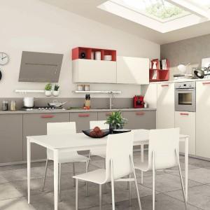 Meble z kolekcji Immagina firmy Lube Cucine. Jadalnia znajduje się w strefie kuchni. Wygodny, prosty w formie stół z komplecie z krzesłami zapewnia wygodne miejsce na rodzinne posiłki i nie tylko. Bieli i szarość zastosowaną zarówno na frontach mebli, jak i na ścianach, podłogach ożywiają elementy w czerwonym kolorze. Nadają przestrzeni również oryginalny charakter.