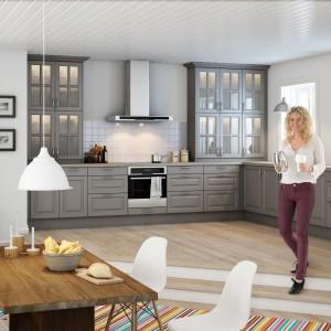 Meble z kolekcji Nice Grå firmy Nettoline. Kuchnia ma charakter otwarty i płynnie łączy się z jadalnia. Obie strefy tworzą wspólne, przestronne wnętrze. Meble wykonane są z drewna i dzięki przeszklonym witrynom mają bardziej salonowy charakter. Dębowy stół i lekkie, białe krzesła doskonale pasuje do szarych frontów.