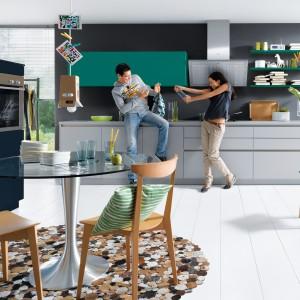 Meble z kolekcji Nova firmy Schüller. W tej kuchni uwagę zwraca zastosowana paleta barw. Fronty mebli mają aż trzy różne kolory. Miejsce na jadalnię wygospodarowano w przestrzeni kuchni. Tworzy ją stół o pięknej, okrągłej formie – szklany blat i noga w kolorze srebra nadają mu również nowoczesny charakter. Proste, drewniane krzesła dopełniły całość.