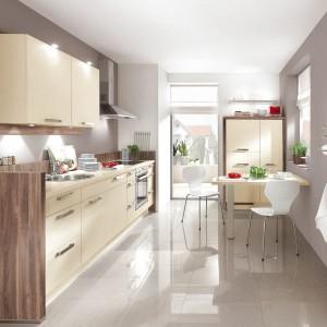 Kuchnia z kolekcji Speed firmy Nobilia. To propozycja do stosunkowo wąskiej kuchni. Meble zajmując głównie całą jedną ścianę, naprzeciwko której ustawiono stół, pełniący rolę jadalni. Jasne fronty dodają kuchni lekkości i optycznie ją powiększają, natomiast elementy w ładnym kolorze drewna ocieplają wnętrze. Ciekawie wykorzystano jedną ze ścian.