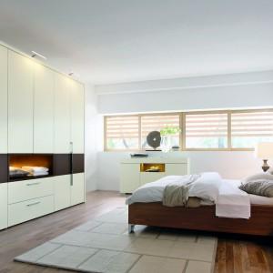 Drewniane łóżko o prostych, minimalistycznym kształcie doskonale komponuje się z pozostałymi, białymi meblami. Fot. Hulsta.