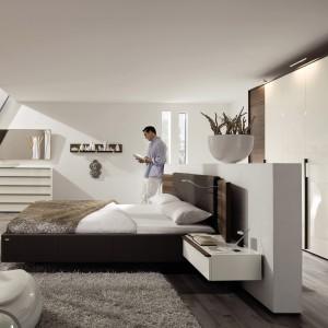 Nowoczesne bryły mebli świetnie prezentują się w towarzystwie jasnych ścian i naturalnych podłóg. Wysoki zagłówek optycznie wydziela strefę spania. Fot. Hulsta.