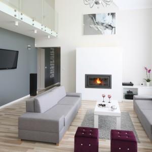 W otwartym na dwie kondygnacje salonie biała zabudowa kominka doskonale wtapia się w nowoczesną aranżację wnętrza. Projekt: Karolina i Artur Urban. Fot. Bartosz Jarosz.