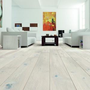 """Deska Gentle z kolekcji Senses dostępna w ofercie firmy Barlinek. Szeroka, jednopasmowa deska barlinecka o delikatnym, kremowo-białym barwieniu. Uszlachetniona procesem szczotkowania oraz zabezpieczona matowym lakierem. Deska warstwowa, czyli tzw. """"engineered wood"""", dzięki swojej konstrukcji nie """"pracuje"""" tak jak lite drewno, a tym samym jest odporna na odkształcania pod wpływem zmian wilgotności otoczenia. Wymiary: 207x2200 mm. Cena: ok. 320  zł/m². Fot. Barlinek."""