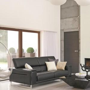 W salonie powieszono futurystyczną huśtawkę. Forma kulistego transparentnego fotela z szarą, dużą poduchą nadaje eleganckiemu salonowi szczypty zwariowanej fantazji. Fot. Łukasz Kozyra.