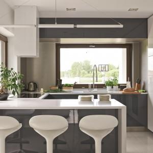 W kuchni, wzorem salonu, panuje minimalistyczny styl. Wnętrze utrzymano w monochromatycznej kolorystyce i prostych formach. Wysoka zabudowa meblowa pozwala na trzymanie wszystkich potrzebnych sprzętów z dala od wzroku domowników i umożliwia utrzymanie porządku. Pomieszczenie ożywa dzięki promieniom słonecznym wpadającym do wnętrza przez duże przeszklenia. Fot. Łukasz Kozyra.