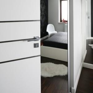 Do sypialni prowadzą białe drzwi, które doskonale komponują się z wysokimi, białymi listwami. Proj. Agnieszka Burzykowska-Walkosz - Studio Formy. Fot. Bartosz Jarosz.