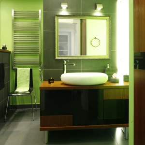 Łazienka została pomalowana farbą w żywym zielonym kolorze, efektownie zestawionym z szarym gresem i miodowym fornirem. Projekt: Agnieszka Żył. Fot. Bartosz Jarosz