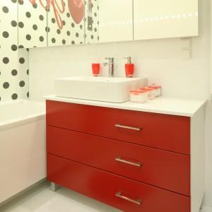 Czerwone akcesoria, motyw czerwonej szminki na fototapecie oraz czerwone fronty szafki to idealna porcja koloru. Dzięki temu łazienka jest pełna energii, ale i stylu.  natomiast biała baza sprawia, ze aranżacja będzie zawsze modna. Projekt: Katarzyna Mikulska-Sękalska. Fot. Bartosz Jarosz.