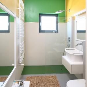 Kilka dogodnych kolorów wykorzystano do pomalowania szerokich pasów ścian u sufitu. Na każdej ścianie zastosowany został inny kolor. We wnęce prysznicowej dominuje zieleń. W tym kolorze jest fragment ściany, a także brodzik prysznicowy wykonany z materiału kompozytowego. Projekt: Konrad Grodziński. Fot. Bartosz Jarosz
