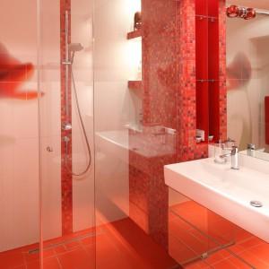 W tej łazience króluje czerwień płytek ceramicznych i mozaiki. Łazienka zawdzięcza swoją kolorystykę znajdującej się obok sypialni utrzymanej w podobnej stylistyce i barwach.  Projekt: Małgorzata Szajbel-Żukowska, Maria Żychiewicz. Fot. Bartosz Jarosz.