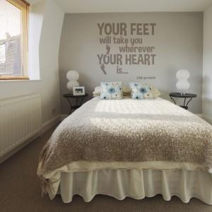 Stonowaną, łagodną sypialnię ożywia napis, który zajmuje sporą część ściany za łóżkiem. Kolor czcionki, kilka tonów ciemniejszy od beżowego tła doskonale dopełnia aranżację sypialni. Fot. Dekornik.