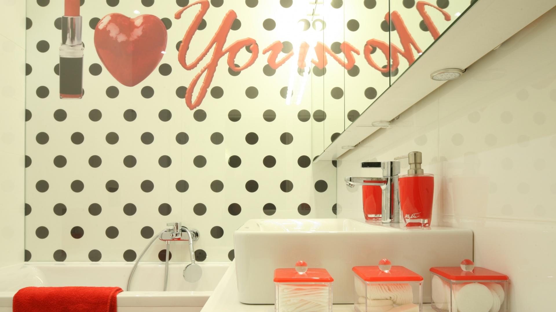 Chociaż na pierwszy rzut oka trudno w to uwierzyć w tej łazience dominuje biel. Jednak za sprawą czerwonych dodatków i efektownej fototapety nad wanna, która wprowadza nieco gwiazdorski klimat, to czerwień decyduje o klimacie i stylu wnętrza. Projekt: Katarzyna Mikulska-Sękalska. Fot. Bartosz Jarosz.