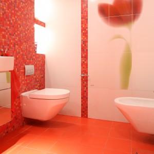 Prawdziwą ozdoba tego wnętrza jest czerwony tulipan - ceramiczna dekoracja w dużym formacie ułożona z kliku płytek. Projekt: Małgorzata Szajbel-Żukowska, Maria Żychiewicz. Fot. Bartosz Jarosz.