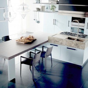 Stół kuchenny niejako wchodzi na wyspę powiększając tym samym przestrzeń roboczą w centrum pomieszczenia. Fot. Fabio Luciani.