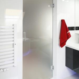 Drzwi do łazienki na poddaszu zostały wykonane na zamówienie z mlecznego szkła – ich kształt musiał być dopasowany idealnie do skosu, a materiał pozwolił zachować lekki charakter aranżacji.  Fot. Bartosz Jarosz.