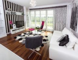 Wnętrze nowoczesne, biało-czarne z elementami drewna egzotycznego.