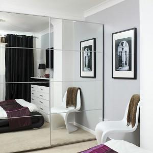 Szafa z lustrzanym frontem nadaje wnętrzu sypialni lekkości i optycznie powiększa przestrzeń. Wrażenie większego pomieszczenia uzyskano również dzięki jasnej kolorystyce poszczególnych elementów wystroju wnętrza, jak beżowa wykładzina i szaro-białe ściany. Fot. Małgorzata Brewczyńska.