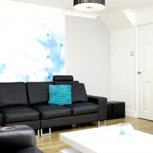 Geometryczna biała ława i lampa-bęben nadają wnętrzu nowoczesnego klimatu, na którym zależało klientom. W nowoczesną stylistykę wpisuje się również abstrakcyjna grafika na ścianie. Fot. Małgorzata Brewczyńska.