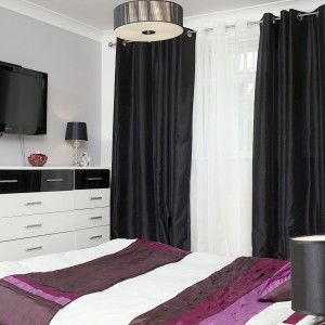Obecność ciężkich, grubych zasłon zapewnia intymność i nadaje wnętrzu domowego klimatu. Czarno-biała komoda i pomalowana na stonowany odcień szarości ściana nawiązują do kolorystyki salonu. Fot. Małgorzata Brewczyńska.