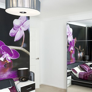 Ścianę za zagłówkiem łóżka pokryto fototapetą, kolorystycznie komponującą się z kolorami łóżka i pokrywającymi je tekstyliami. Fot. Małgorzata Brewczyńska.