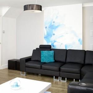 Monochromatyczny czarno-biały salon z delikatnymi kolorowymi akcentami ocieplono podłogą w kolorze naturalnego drewna. Fot. Małgorzata Brewczyńska.