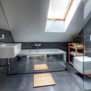 Przestrzeń łazienki ociepla wpadające przez okno światło dzienne oraz drewniane akcenty w postaci półek na kosmetyki i, utrzymanej w tej samej kolorystyce, drewnianej kratki na podłodze. Fot. Vostok Design.