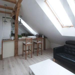 Salon i kuchnia stanowią wspólną przestrzeń, oddzielana umownie przez podtrzymującą strop drewnianą belkę i półwysep kuchenny. Ten z kolei może pełnić funkcję niewielkiego, praktycznego baru. Fot. Vostok Design.