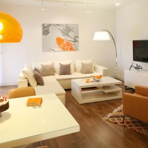 Fotel w kolorze słodkiego karmelu, obrazy w ciepłych barwach oraz pomarańczowa lampa subtelnie ożywiają jasną aranżację. Projekt: Małgorzata Galewska. Fot. Bartosz Jarosz.