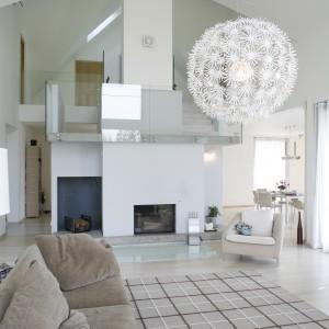 Bezowa kanapa i zbliżony kolorystyka dywan w kratę sprawiają, ze jasne wnętrze zyskuje przytulny wygląd. Projekt: Alina Grzybowska, Konstanty Jeżewski. Fot. Bartosz Jarosz.
