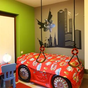 Punktem wyjścia aranżacji pokoju kilkuletniego chłopca jest ściana przy łóżku. Umieszczono na niej wizerunek Batmana, pędzącego na ratunek światu między wieżowcami Nowego Yorku. Fan niesamowitego bohatera musi mieć też niesamowite łóżko. To, w kształcie czerwonego samochodu jest nie tylko efektowne, ale i bardzo wygodne. I co ważne – wzbudza zachwyt innych chłopców, nie tylko małych. Projekt: Monika Włodarczyk, Jarosław Jończyk. Fot. Bartosz Jarosz.