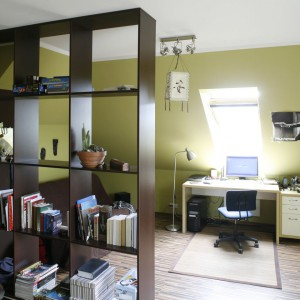 Przestrzeń pokoju na poddaszu została sprytnie rozdzielona za pomocą szafy i regału, na strefę garderobianą i bardziej prywatną. Wyposażenie tej drugiej stanowi niewielka sofa rozkładana w brązowym kolorze, służąca jako łóżko. Biurko ustawiono w najjaśniejszym miejscu pokoju, czyli przy oknie dachowym, zapewniającym optymalne oświetlenie w ciągu dnia. Projekt: Joanna Wojtkielewicz. Fot. Bartosz Jarosz.