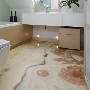 Łazienka ulokowana jest pod skosami. Ze względu na to że kształt pomieszczenia jest nieregularny główną dekoracją stanowi podłoga-obraz. Wybrano piękny onyks z rysunkiem  przenikających się barw. Fot. Bartosz Jarosz.