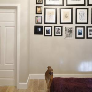 Jedną ścianę w sypialni wykorzystano jako miejsce na domową galerię. Zdjęcia umieszczone w ramkach o rożnych formatach tworzą ciekawą dekorację. Projekt: Monika Gorlikowska. Fot. Bartosz Jarosz.