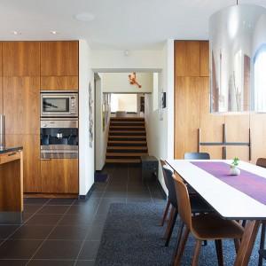 Ściany w kuchni wykończono drewnianą okładziną. Drewniana jest także kuchenna obudowa, w którą wkomponowano sprzęt AGD. Przestrzeń jadalni została umownie zaznaczona obecnością miękkiego dywanu, który jednak utrzymano w kolorystyce podłogi. Fot. Per Jansson.