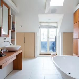W dużej łazience dominuje biel, ocieplona delikatnymi akcentami z drewna. Pięknie okrągła wolno stojąca wanna i dwie nablatowe umywalki oraz obecność drewna nadają łazience charakteru ekskluzywnego salonu kąpielowego. Fot. Per Jansson.
