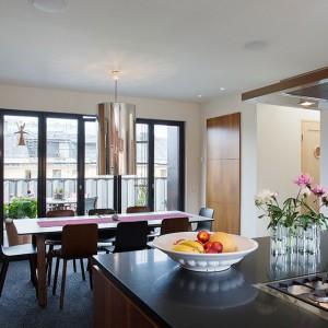 Obszerna przestrzeń kuchni i jadalni zachwyca mariażem delikatnych kolorów z ciemniejszymi, intensywnymi barwami. Powierzchnie wykończone na połysk dodatkowo nadają wnętrzu elegancji. Fot. Per Jansson.