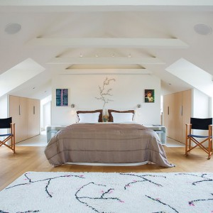 Piękną dużą sypialnię wykończono w jasnych barwach. Nad łóżkiem i dywanem mamy korespondujące ze sobą roślinne motywy. Ścianka za łóżkiem stanowi element wspólny sypialni i okazałej łazienki, do której prowadzi komunikacja po obu stronach łóżka. Fot. Per Jansson.