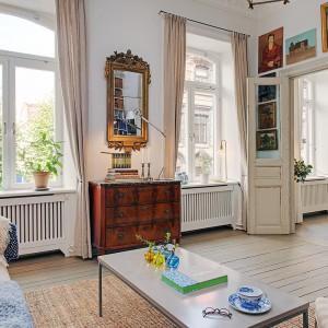 Wysokie okna w salonie zapewniają bogaty dostęp dziennego światła. Fot. Alvhem Makleri.