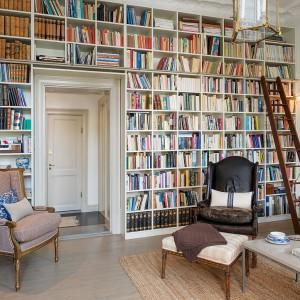 Wysoką ścianę w salonie w całości zabudowano półkami. Powstały regał wykorzystano jako imponującą, dużą biblioteczkę. Fot. Alvhem Makleri.