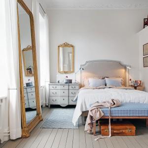 W sypialni dominują jasne kolory: szarości na podłodze i niewielkiej komodzie, biel na ścianach i pastelowy błękit w postaci tkanin na łóżku. Ich chłodną barwę przełamują ciepłe drewniane akcenty i pozłacane ramy luster. Fot. Alvhem Makleri.