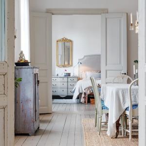 Trzy pokoje zlokalizowane w jednym rzędzie dzielą i łączą podwójne drzwi - element pozostały z oryginalnego wyposażenia mieszkania. Fot. Alvhem Makleri.