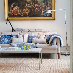 W salonie przytulny klimat tworzy kanapa z wieloma poduszkami. Wzorzyste tkaniny w niebieskim kolorze ożywiają wnętrze i stanowią ciekawą kolorystyczną kompozycję z pozłacaną ramą naściennego obrazu. Fot. Alvhem Makleri.