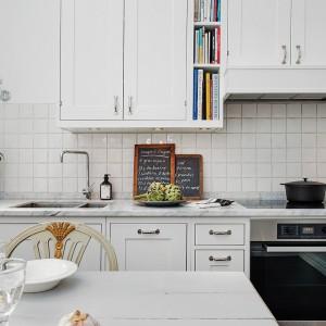 Kuchnię utrzymano w skandynawskim stylu. Jest nie tylko biało i jasno, ale też funkcjonalnie i praktycznie. Nad blatem kuchennym, wykonanym z marmuru zamontowano przydatne oświetlenie z funkcją przyciemnienia. Fot. Alvhem Makleri.