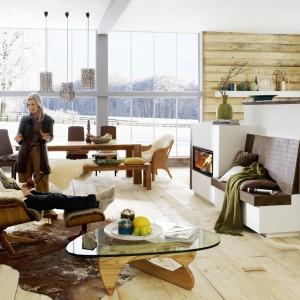 Podłoga i ściana wykończona drewnem, w połączeniu z ciepłem kominka sprawiają, że nowoczesne wnętrze staje się przytulne. Aranżację uzupełniają naturalne meble. Fot. Brunner.