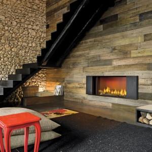 Ściana wykończona deskami o różnym wybarwieniu, w połączeniu z ogniem kominka Klee marki MCZ to duet, który nadaje wnętrzu uroku. Fot. MCZ.